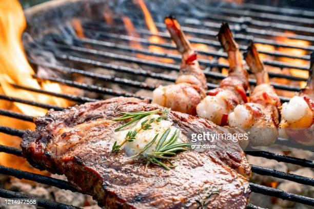 a delicious ribeye steak and bacon wrapped shrimp on a flaming hot grill - shrimp seafood stock pictures, royalty-free photos & images