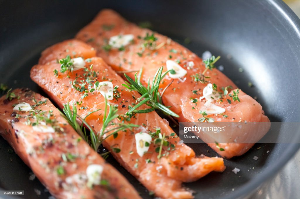 Delicious salmon fillet in a pan with garlic and herbs : Foto de stock