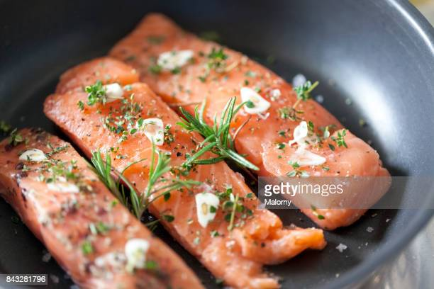 delicious salmon fillet in a pan with garlic and herbs - seafood stock pictures, royalty-free photos & images