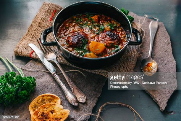 Delicious stew dish, decorated with slices roasted potato and fresh parsley