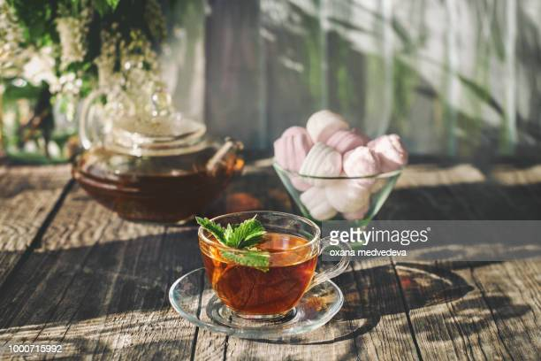 Delicious strawberry green mint tea in a transparent glass teapot and Cup in the summer, on a...