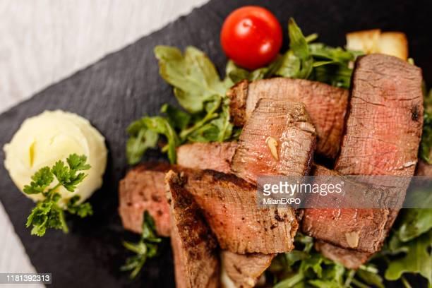 黒い石板に美味しいタリアタステーキ - ステーキハウス ストックフォトと画像