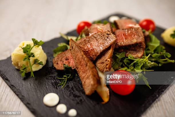 delicious tagliata steak on black stone plate - carne de churrasco imagens e fotografias de stock