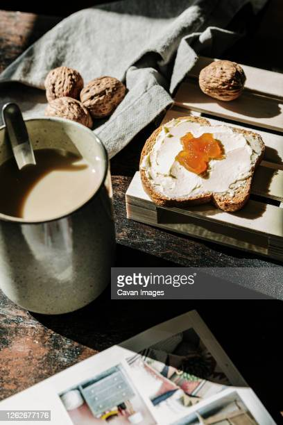 delicious toast with butter and jam, near to a coffee cup and walnuts - nuts magazine stock pictures, royalty-free photos & images
