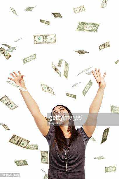 Delighted brunette tries to catch many falling dollars