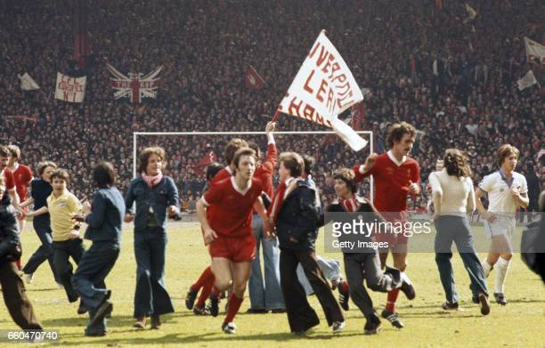 Delighted flared clad young fans swarm the pitch as Jimmy Case and Terry McDermott and West Ham player Geoff Pike leave the field as the Kop wave...