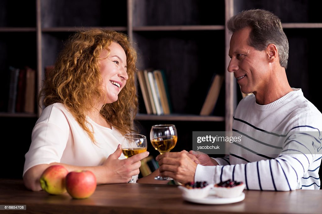 Delighted grandparents looking at each other and holding hands : Stock Photo