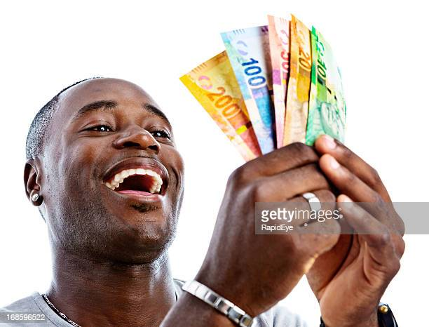 delighted man holds sheaf of new south african banknotes - south african currency stock photos and pictures