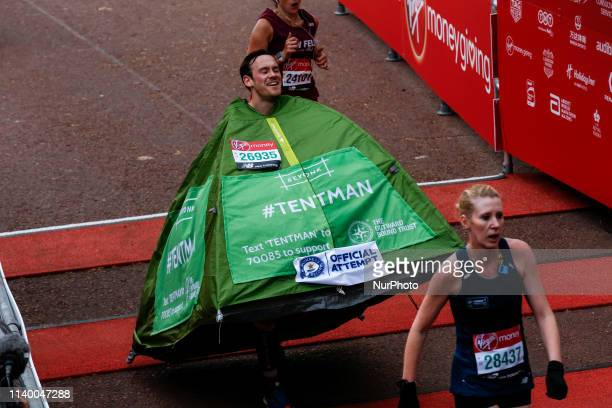 Delighted man running as a tent crosses the finish line during the Virgin Money London Marathon in London England on April 28 2019 Nearly 43 thousand...