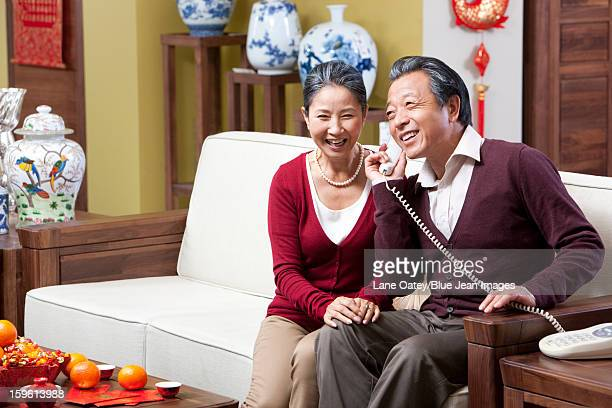 Delighted senior couple on the phone during Chinese New Year