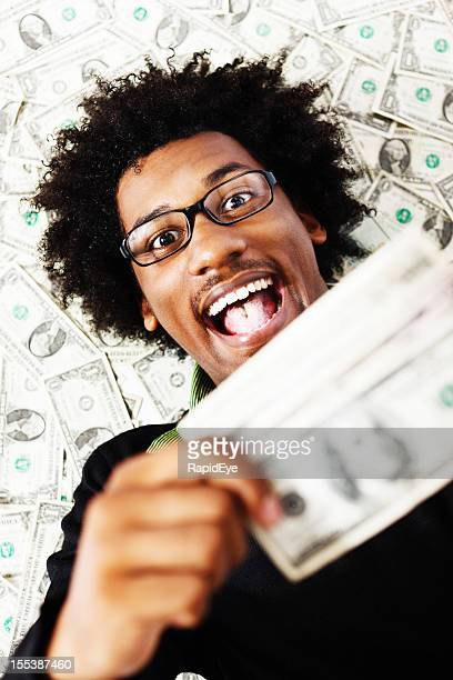Delighted young man with lots of US dollars