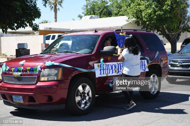 Delilah Juarez receives a gift during a birthday parade held in her honor hosted by Tyler Robinson Foundation in front of her home on May 25 2020 in...