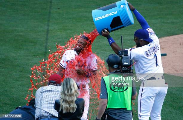 Delino DeShields is doused with Powerade by teammate Elvis Andrus of the Texas Rangers following the team's 87 win over the Oakland Athletics at...