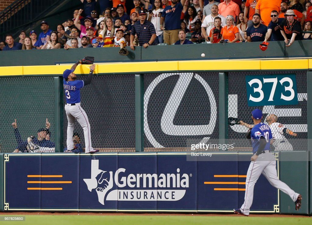 Delino DeShields #3 of the Texas Rangers and Nomar Mazara #30 watch as Brian McCann #16 of the Houston Astros hits a home run in the fourth inning at Minute Maid Park on May 12, 2018 in Houston, Texas.