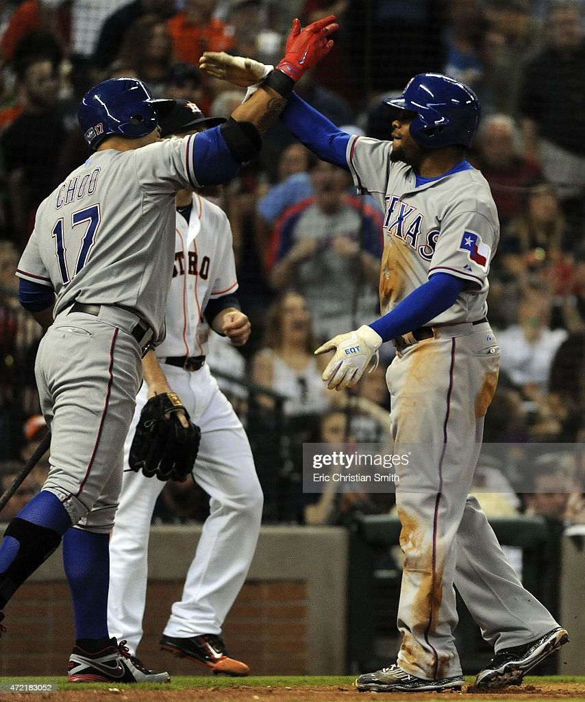 Delino DeShields #7 of the Texas Rangers celebrates his game-tying run with Shin-Soo Choo during the eighth inning against the Houston Astros at Minute Maid Park on May 4, 2015 in Houston, Texas.