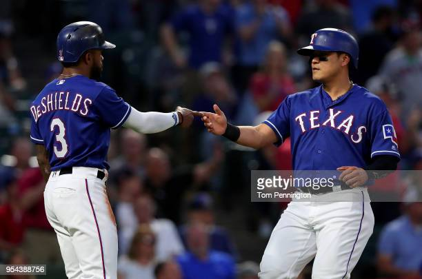 Delino DeShields of the Texas Rangers celebrates with ShinSoo Choo of the Texas Rangers after the pair scored against the Boston Red Sox in the...