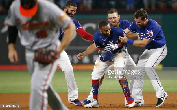 Delino DeShields of the Texas Rangers celebrates with teammates after DeShields drove in the winning run to defeat the Baltimore Orioles 21 in twelve...