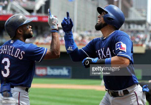 Delino DeShields of the Texas Rangers congratulates teammate Robinson Chirinos on a tworun home run against the Minnesota Twins during the third...
