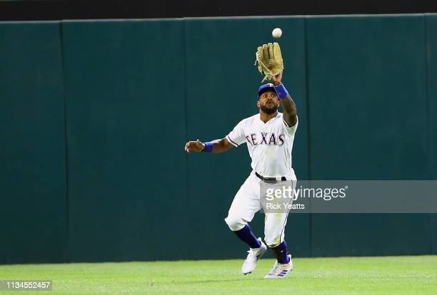 Delino DeShields of the Texas Rangers fields a fly ball to center field in the sixth inning against the Houston Astros at Globe Life Park in...