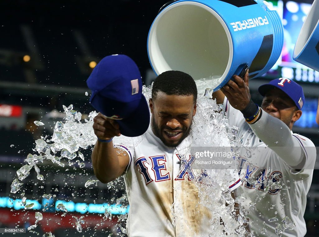 Delino DeShields #3 of the Texas Rangers gets showered with water by Elvis Andrus #1 of the Texas Rangers after the 5-3 win over the Seattle Mariners at Globe Life Park in Arlington on September 11, 2017 in Arlington, Texas.
