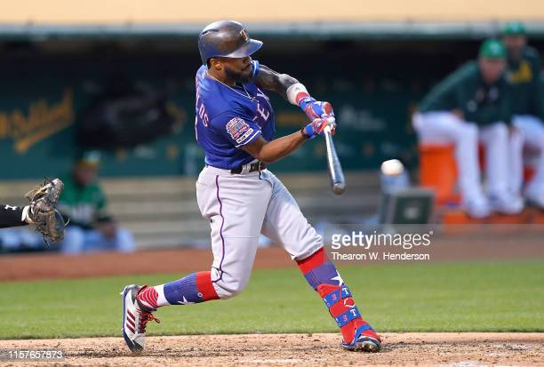 Delino DeShields of the Texas Rangers hits an rbi singles scoring Logan Forsythe against the Oakland Athletics in the top of the fifth inning at Ring...