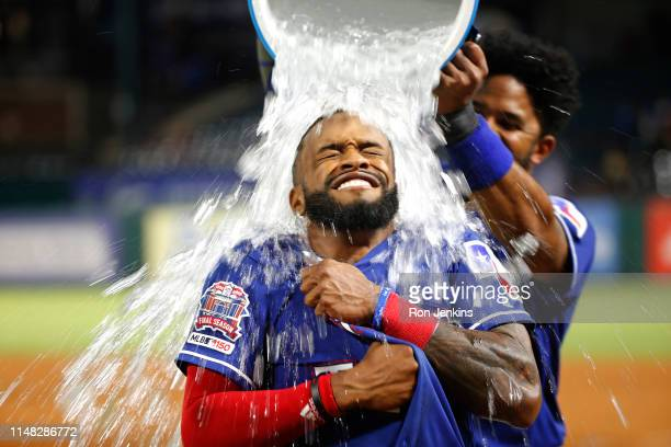 Delino DeShields of the Texas Rangers is doused by teammate Elvis Andrus after DeShields drove in the winning run to defeat the Baltimore Orioles 21...