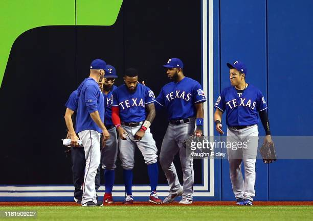 Delino DeShields of the Texas Rangers is tended too by teammates after catching Reese McGuire of the Toronto Blue Jays out in the fourth inning...