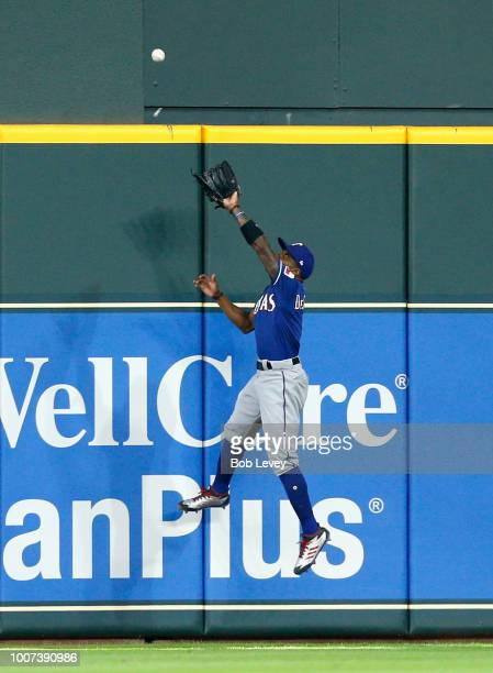 Delino DeShields of the Texas Rangers leaps at the wall but is unable to catch a fly ball by JD Davis of the Houston Astros in the seventh inning at...