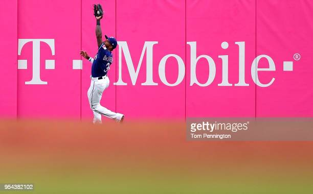 Delino DeShields of the Texas Rangers pulls in a fly ball hit by Eduardo Nunez of the Boston Red Sox in the top of the second inning at Globe Life...