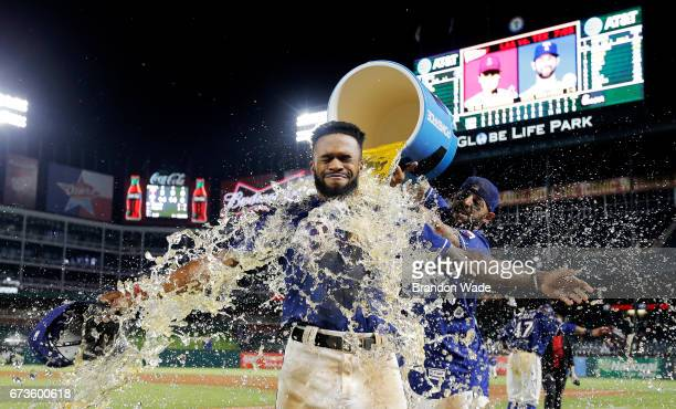 Delino DeShields of the Texas Rangers receives a sports drink bath from Rougned Odor in celebration of a 143 win over the Minnesota Twins at Globe...