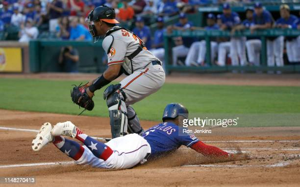 Delino DeShields of the Texas Rangers slides head first into home plate to score as Pedro Severino of the Baltimore Orioles waits on the throw during...