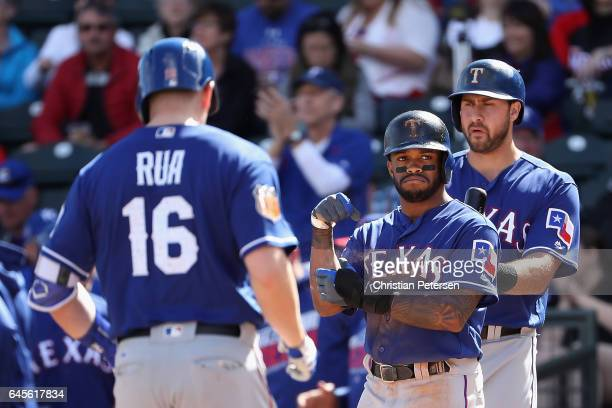 Delino DeShields of the Texas Rangers waits at home plate to congratulate Ryan Rua after Rua hit a tworun home run against the Kansas City Royals...