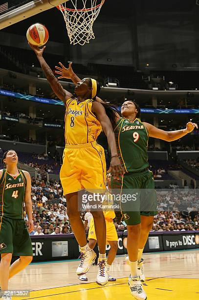 Delisha MiltonJones of the Los Angeles Sparks goes up for a layup as Kelly Santos of the Seattle Storm attempts to block the shot on September 14...