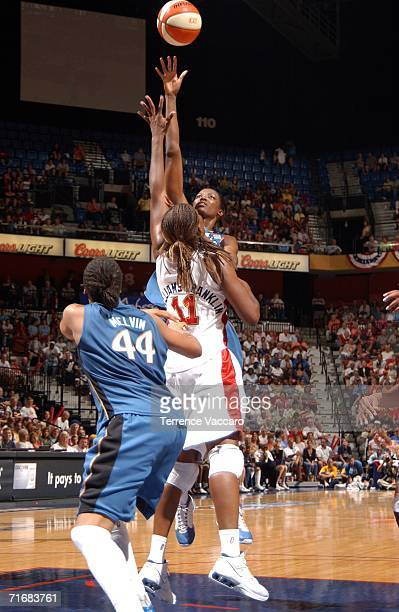 DeLisha MiltonJones of the Washington Mystics shoots against Taj McWilliamsFranklin of the Connecticut Sun in game two of the Eastern Conference...