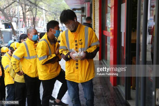 Deliverers from different companies line up for free meals provided by a local restaurant in Zhengzhou in central China's Henan province Sunday,...