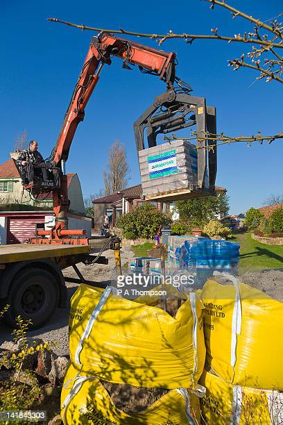 delivering building materials by crane - construction material stock pictures, royalty-free photos & images