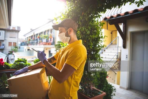 entregando comida à sua porta mantendo o distanciamento social durante o surto de covid-19 - carteiro - fotografias e filmes do acervo
