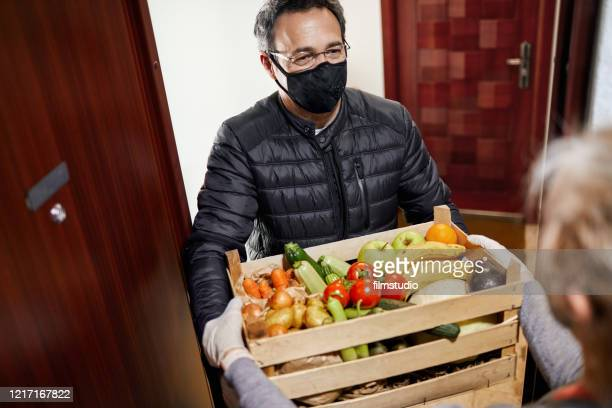 delivering food during coronavirus lockdown - helping hand stock pictures, royalty-free photos & images