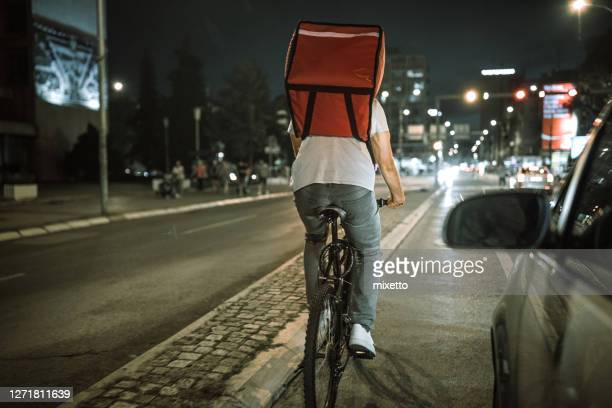 delivering food on bicycle in city at night - evening meal imagens e fotografias de stock