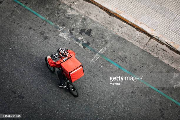 delivering food on bicycle in city - food stock pictures, royalty-free photos & images