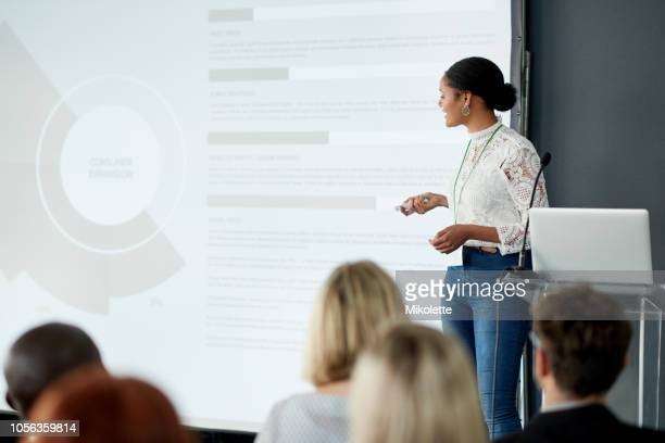 delivering informative presentations is what she does best - presenter stock pictures, royalty-free photos & images
