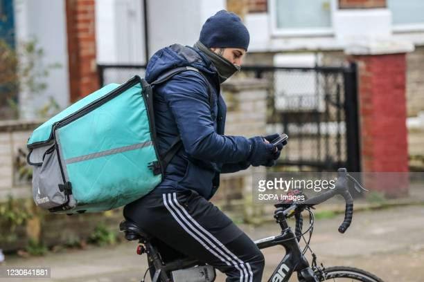 Deliveroo bike rider checks his mobile phone in London.
