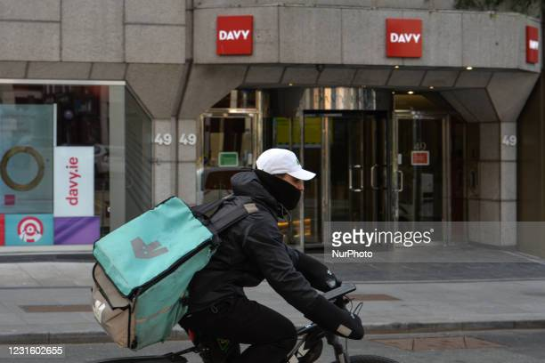 Deliveroo courier cyckles by Davy headquarters in Dawson Street in Dublin. Davy is Ireland's largest stockbroker, wealth manager, asset manager and...