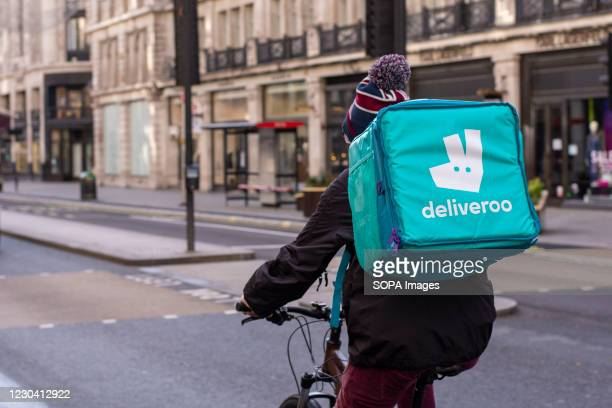 Deliveroo courier rides along the Regent Street delivering Takeaway food in central London during covid 19 tier 4 restrictions.