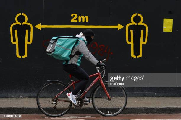 Deliveroo currier cycles by a 2m social distancing sign seen on a wall in Dublin during Level 5 Covid-19 lockdown. On Tuesday, 26 January in Dublin,...