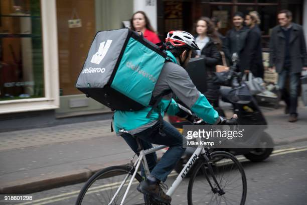 Deliveroo cycle courier with his large back box while out delivering in London England United Kingdom
