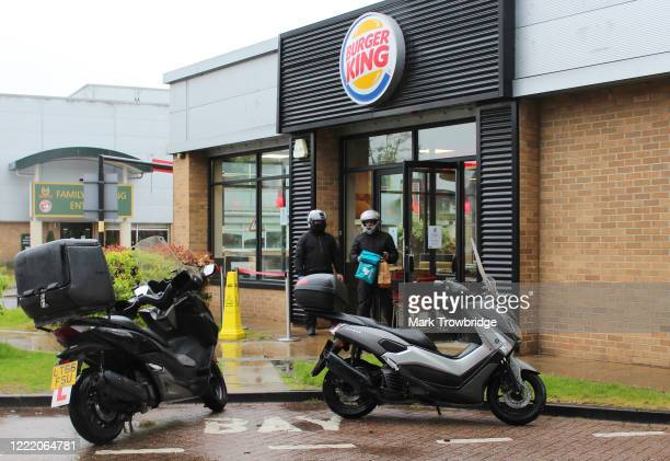 Deliveroo driver picks up a food order from a re-opened Burger King restaurant operating on a delivery only basis in the London Borough of Merton on...