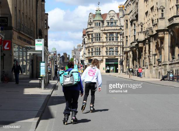 Deliveroo employees on rollerblades skate through an empty street on May 02, 2020 in Oxford, England. British Prime Minister Boris Johnson, who...