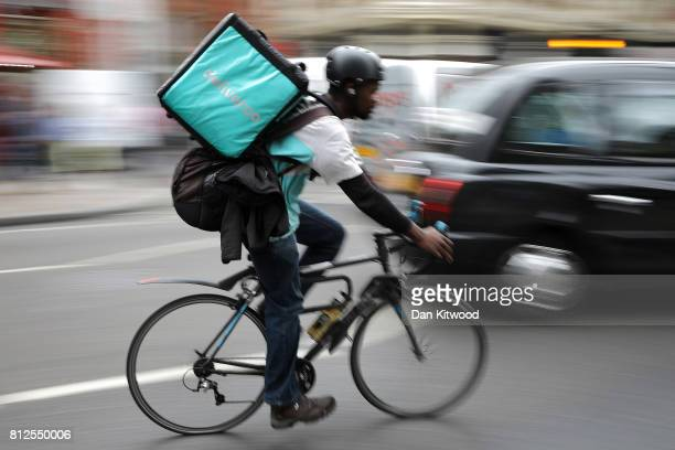 Deliveroo rider cycles through central London on July 11 2017 in London England A recent government review looking at the 'Gig Economy' the 'Taylor...