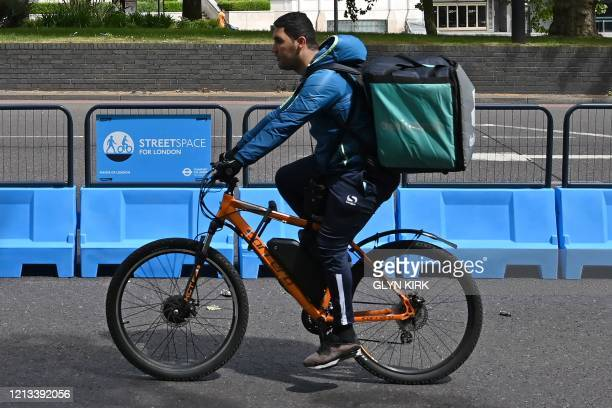 """Deliveroo rider makes use of a new expanded cycle lane, """"streetspace for London"""" on Park Lane in London on May 17 following an easing of lockdown..."""